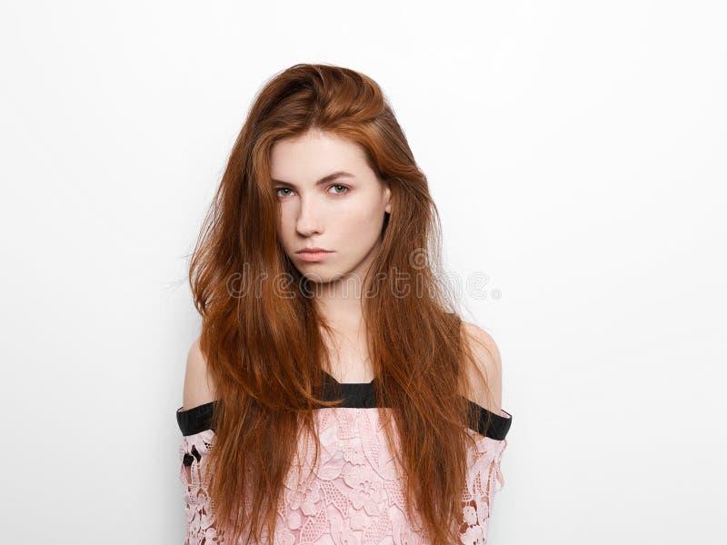 Молодая красивая excited женщина с шакшевать дыханием, с шикарными естественными волосами имбиря, пустой космос экземпляра на бел стоковое фото