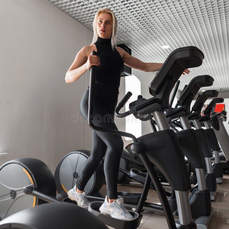 Молодая красивая sporty женщина в черных стильных одеждах в тапках делает cardio тренировку на имитаторе в спортзале Худенькая де стоковое фото rf