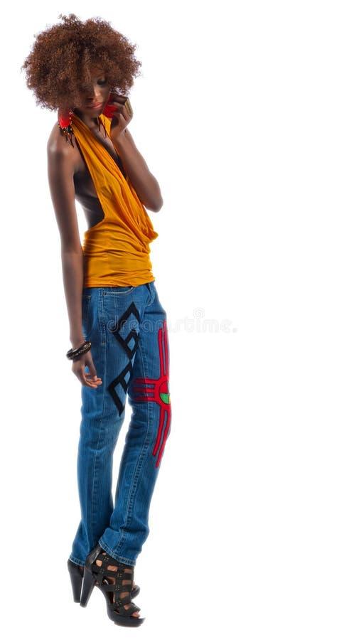 Молодая красивейшая чернокожая женщина в джинсыах стоковое фото rf