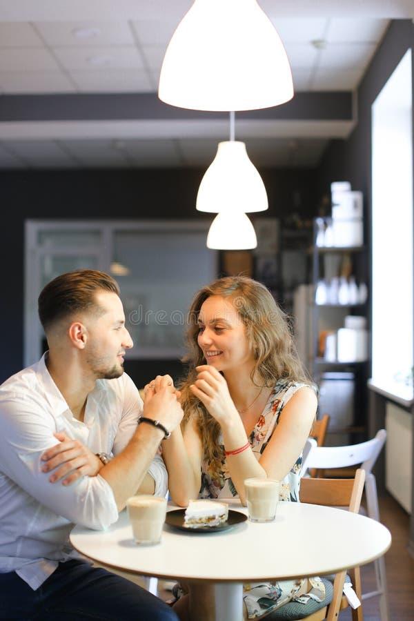 Молодая красивые девушка и мальчик сидя на кафе около вкусного торта и держа руки стоковое фото