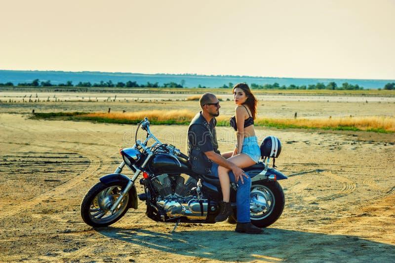 Молодая красивые женщина и человек сидя на мотоцикле стоковое изображение