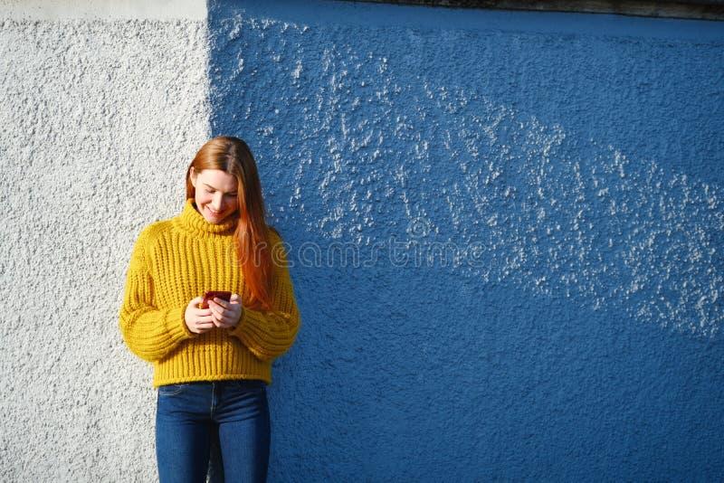 Молодая красноголовая женщина отправляет текстовое сообщение с телефоном снаружи стоковые изображения rf