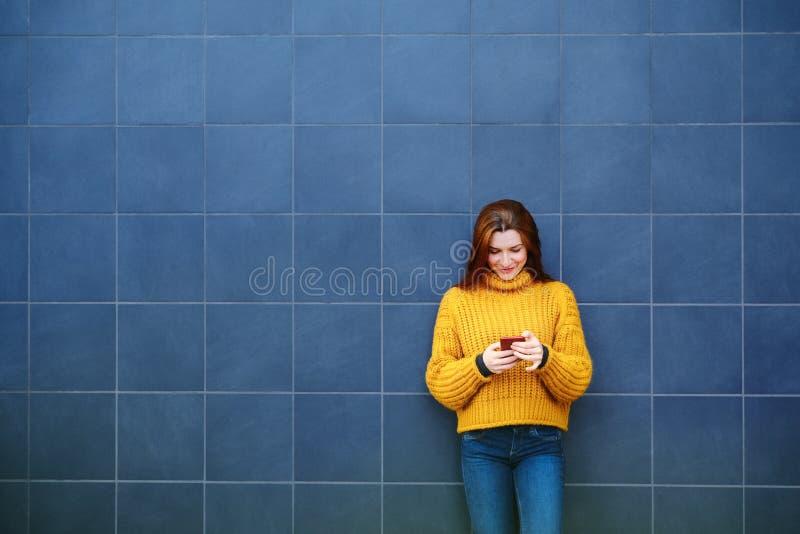 Молодая красноголовая женщина отправляет текстовое сообщение с телефоном снаружи стоковое фото rf