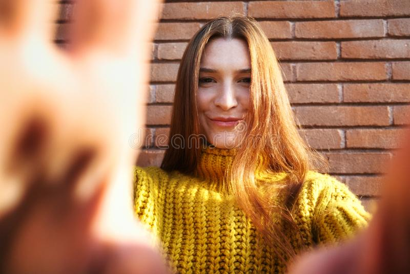 Молодая красноголовая женщина, прикрывающая камеру с руками стоковые изображения