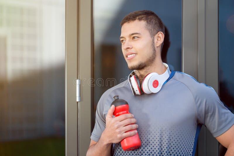 Молодая латинская бутылка с водой человека смотря думая день мечтая фитнес тренировки спорт космоса экземпляра copyspace бегуна б стоковые фотографии rf