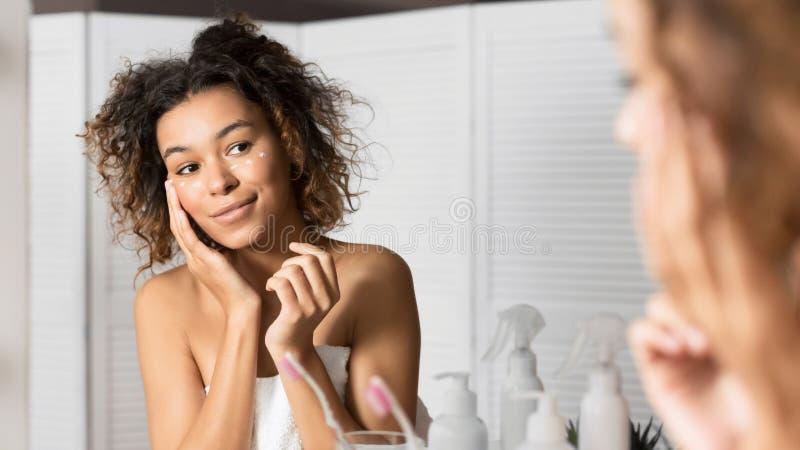 Молодая леди под глазами подает крим, глядя в зеркало в ванной стоковая фотография rf