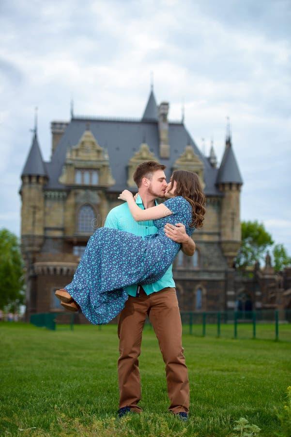 Молодая любящая пара идя близко замка Отключение свадьбы к медовому месяцу стоковые фотографии rf