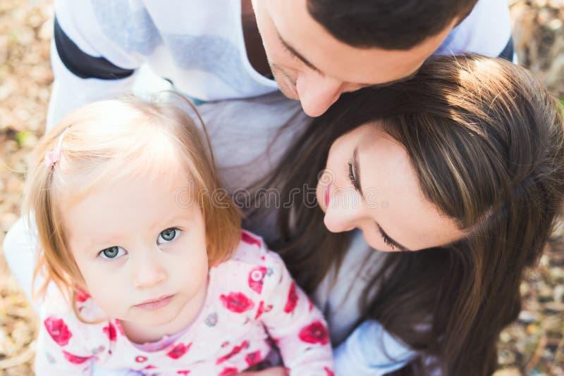 Молодая любящая семья из трех человек, подлинный беспристрастный портрет семьи outdoors стоковое фото