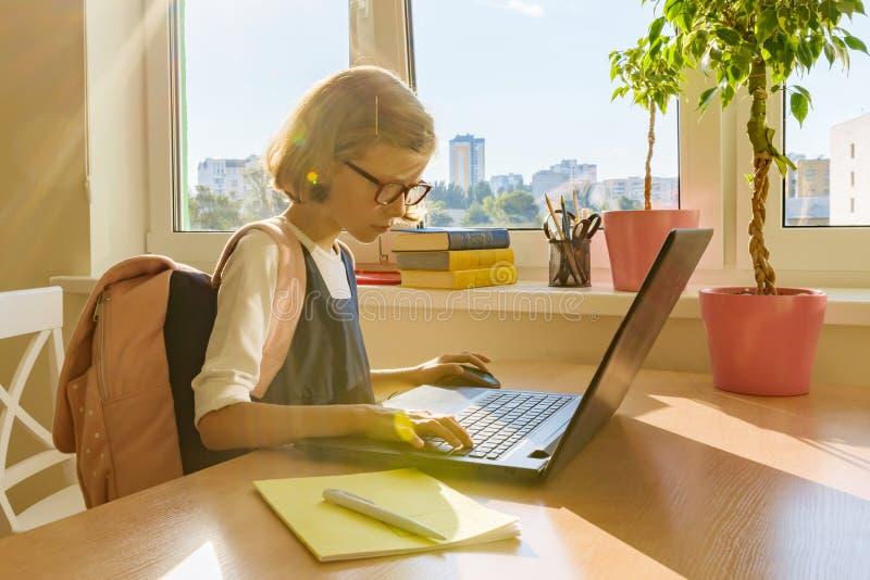 Молодая маленькая девочка в стеклах при рюкзак школы работая на компьютере, компьтер-книжка хакера стоковые изображения rf