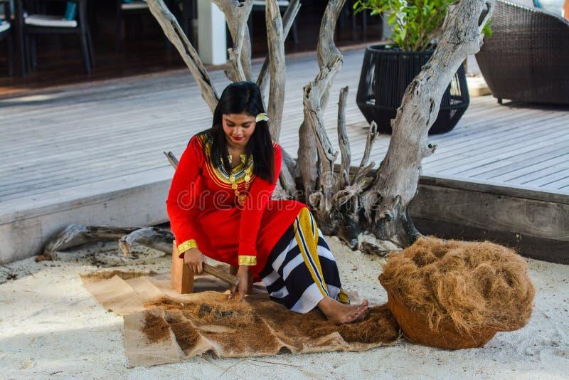 Молодая мальдивская девушка в красных национальных одеждах работая на незрелости стоковые изображения