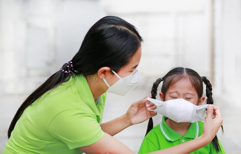 Молодая мама нося защитную маску для ее дочери пока снаружи к против премьер-министру 2 загрязнение воздуха 5 в городе Бангкока r стоковая фотография