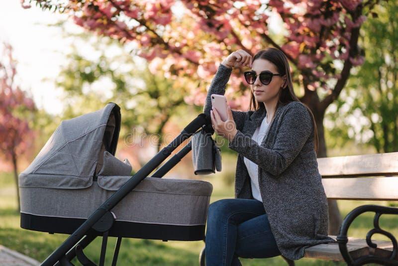 Молодая мама сидя на стенде с ее младенцем в прогулочной коляске и телефоне пользы Mothe смотрит что-то в интернете стоковое фото