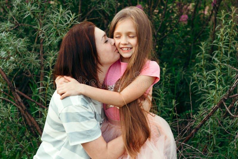 Молодая мама целует ее меньшую дочь на щеке против зеленой предпосылки на солнечный летний день стоковое изображение rf