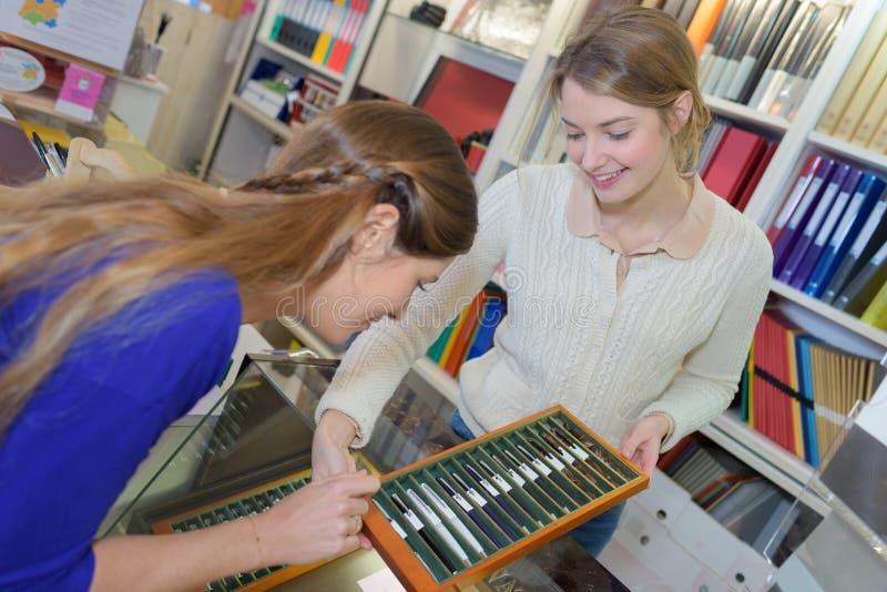 Молодая мать выбирая канцелярские принадлежности школы в магазине стоковое фото rf