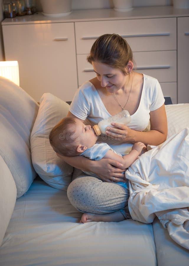 Молодая мать давая бутылку молока к ее голодному младенцу на ноче стоковое изображение rf