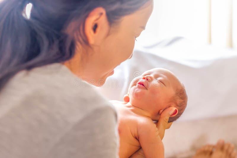 Молодая мать держа ее маленький newborn ребенка стоковое фото rf
