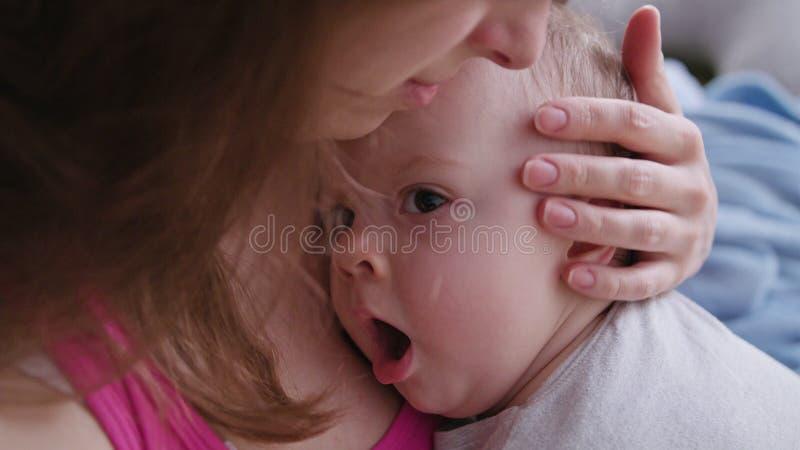 Молодая мать держа ее младенца в ее оружиях стоковая фотография