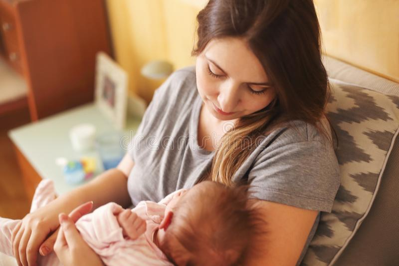 Молодая мать держа ее новорожденный ребенка Младенец ухода мамы Семья стоковая фотография rf