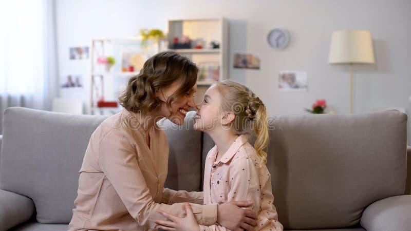 Молодая мать и дочь нюхая сидеть на софе, отношения близких родственников, любовь стоковая фотография