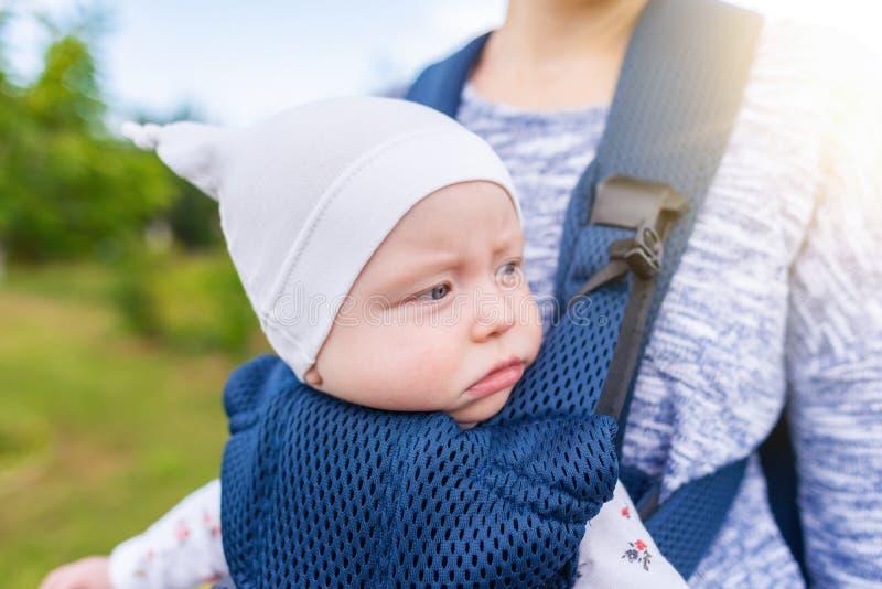 Молодая мать и ее ребенок в несущей младенца стоковые изображения rf