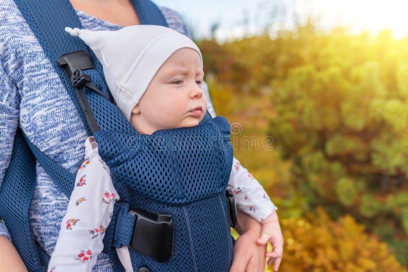 Молодая мать и ее ребенок в несущей младенца стоковое изображение