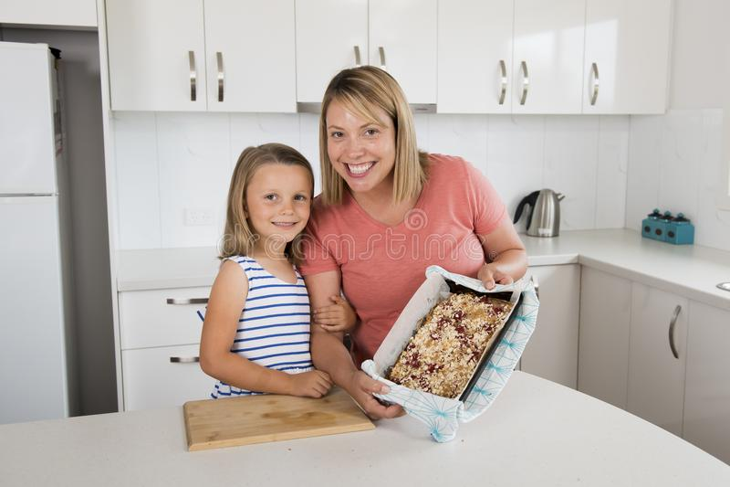 Молодая мать и ее сладостные красивые 7 лет старой дочери показывая гордый торт клубники после печь совместно дома smil кухни стоковые фото
