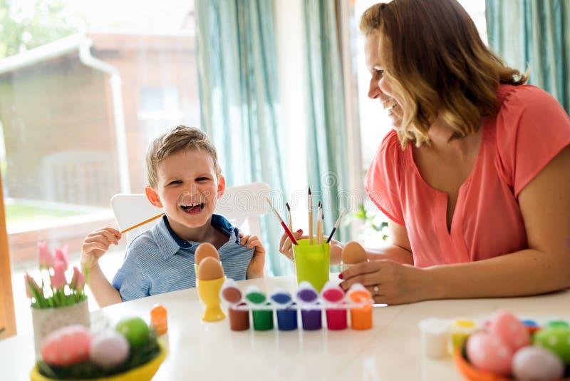 Молодая мать и ее сын имея потеху пока красить eggs для пасхи стоковые изображения rf