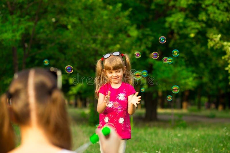Молодая мать и маленькая дочь играя в парке с пузырями мыла стоковые фото
