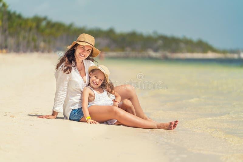 Молодая мать и маленькая дочь наслаждаясь пляжем в Доминиканской Республике стоковое фото
