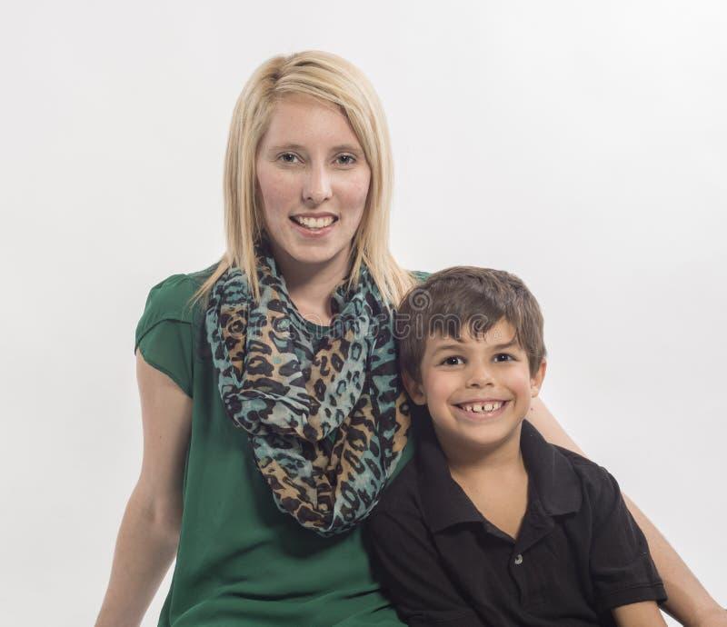 Молодая мать и межрасовый сын на белой предпосылке стоковые фото