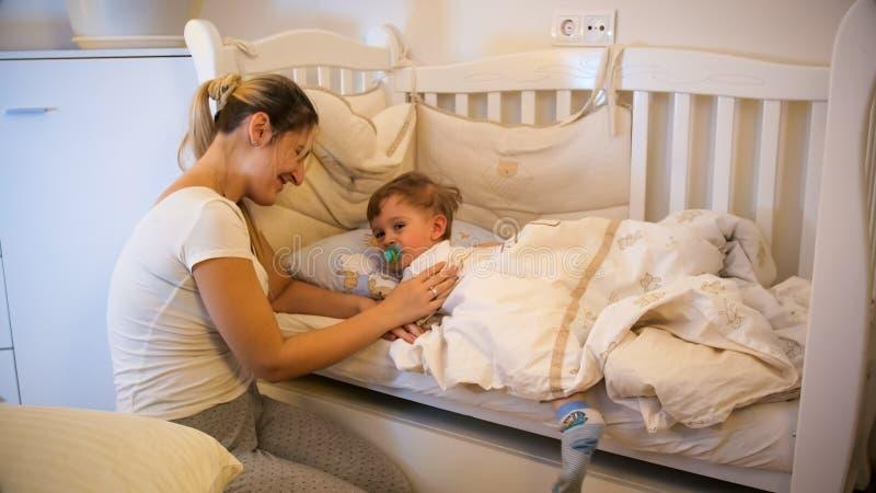 Молодая мать лаская ее плача сына малыша лежа в кровати на ноче стоковые изображения rf