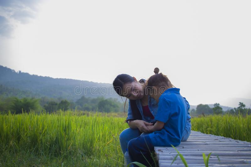 Молодая мать обнимая и успокаивая плача маленького длинного мальчика волос, азиатской матери пробуя утешить и утихомирить вниз ее стоковые изображения rf