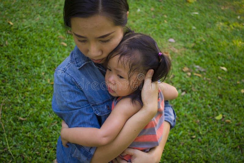 Молодая мать обнимая и успокаивая плача маленькую дочь, азиатскую мать пробуя утешить и утихомирить вниз ее плача ребенка стоковая фотография rf