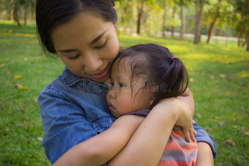 Молодая мать обнимая и успокаивая плача маленькую дочь, азиатскую мать пробуя утешить и утихомирить вниз ее плача ребенка стоковая фотография