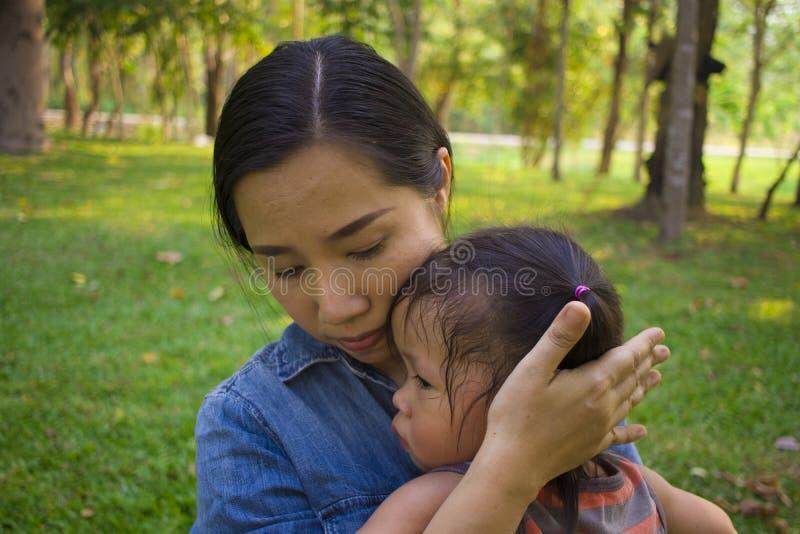 Молодая мать обнимая и успокаивая плача маленькую дочь, азиатскую мать пробуя утешить и утихомирить вниз ее плача ребенка стоковое изображение rf