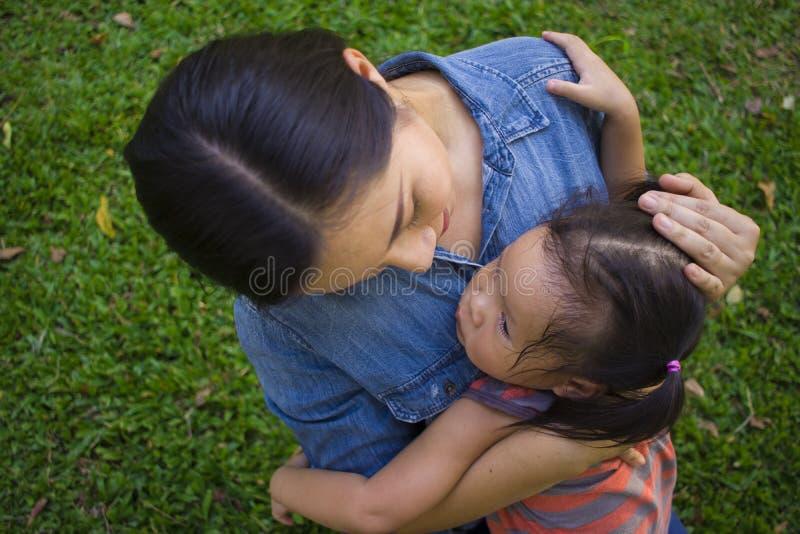 Молодая мать обнимая и успокаивая плача маленькую дочь, азиатскую мать пробуя утешить и утихомирить вниз ее плача ребенка стоковое фото