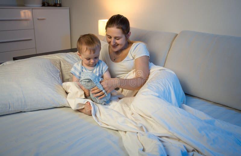 Молодая мать при ребёнок лежа в кровати и играя с игрушкой стоковые изображения