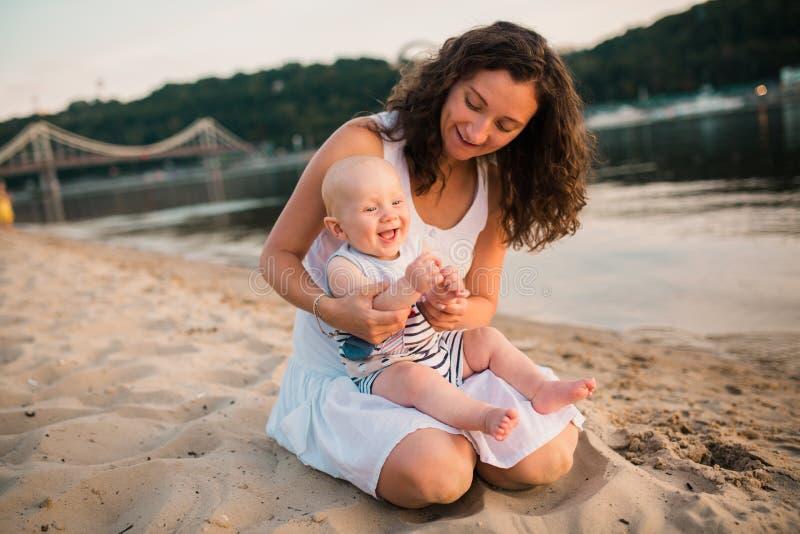 Молодая мать сидя на пляже с годовалым сыном младенца Мальчик обнимая, усмехающся, смеющся, летний день Счастливое детство беспеч стоковые фотографии rf