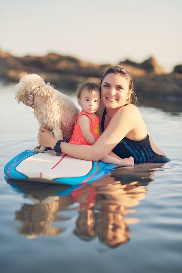 Молодая мать с ребенком на доске прибоя стоковая фотография