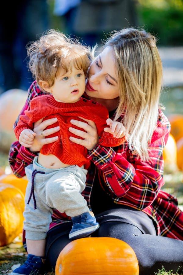 Молодая мать с ребенком на lawm с тыквы стоковое фото