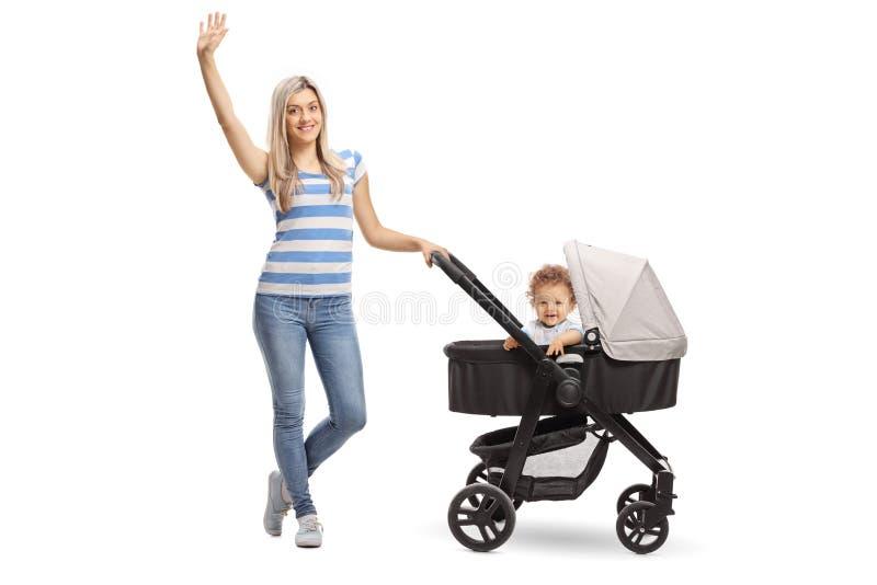 Молодая мать с ребёнком в прогулочной коляске развевая на камере стоковая фотография