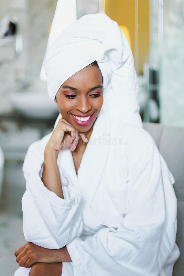 Молодая милая афро американская девушка сидя в bathroom и нося белом купальном халате стоковые изображения rf