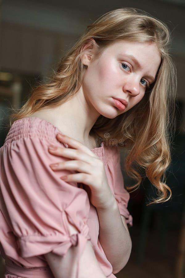 Молодая милая белокурая девушка с голубыми глазами в розовом платье, опрокидывающ голову, держащ руку на комоде и смотрящ в камер стоковое фото rf