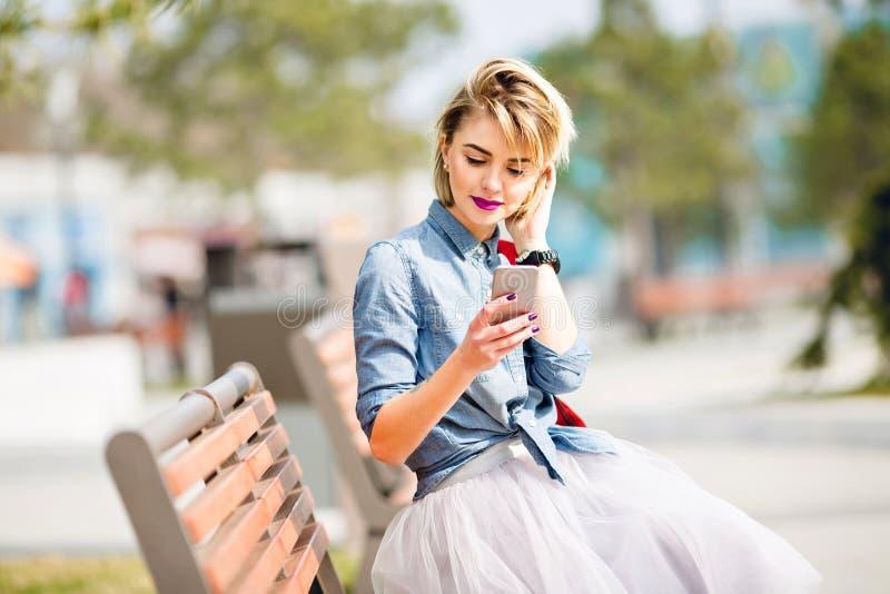 Молодая милая белокурая девушка с короткими волосами сидя на деревянной скамье и смотря рубашку джинсовой ткани смартфона нося го стоковая фотография rf