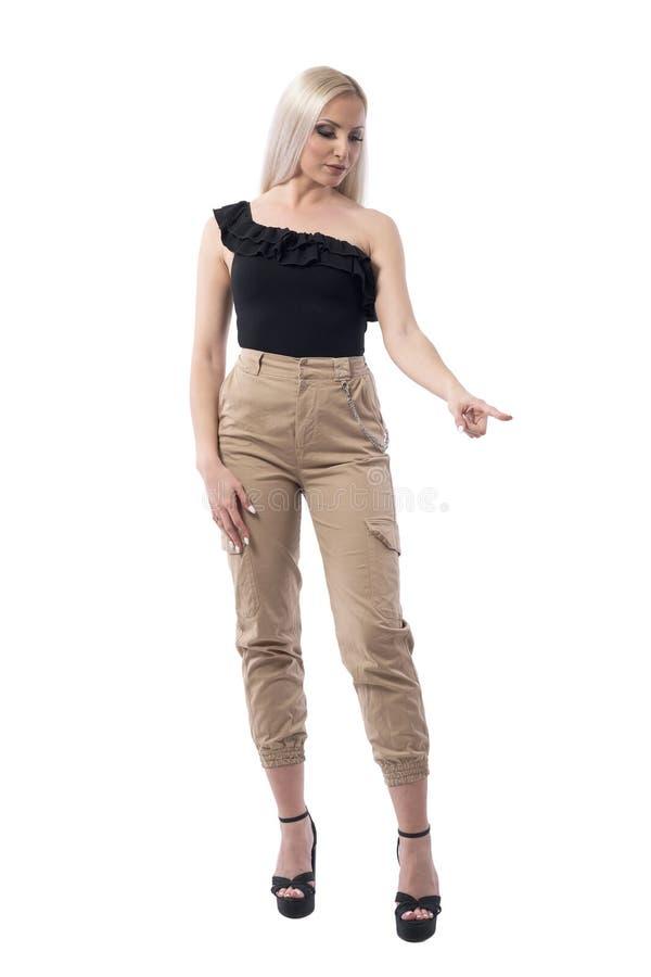 Молодая милая белокурая женщина указывая палец вниз с выбирать и выбора пока ходящ по магазинам стоковая фотография rf
