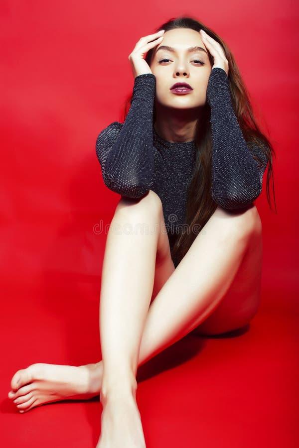 Молодая милая дама в сияющем bodysuit представляя на красной предпосылке, концепции людей образа жизни стоковая фотография rf