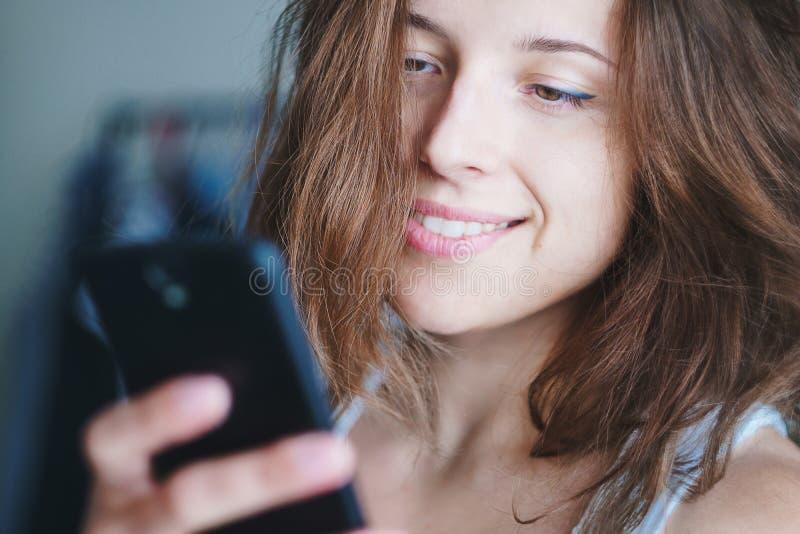 Молодая милая дама с карими глазами и каштановыми волосами каштана смотря ее экран смартфонов усмехаясь в романтичном пути стоковая фотография rf