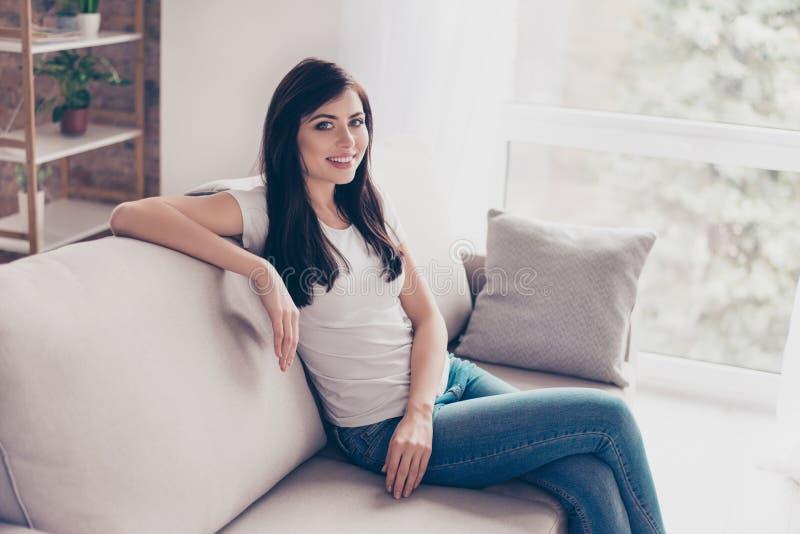 Молодая милая девушка брюнет расслабляющий дома сидеть на славном s стоковые фотографии rf