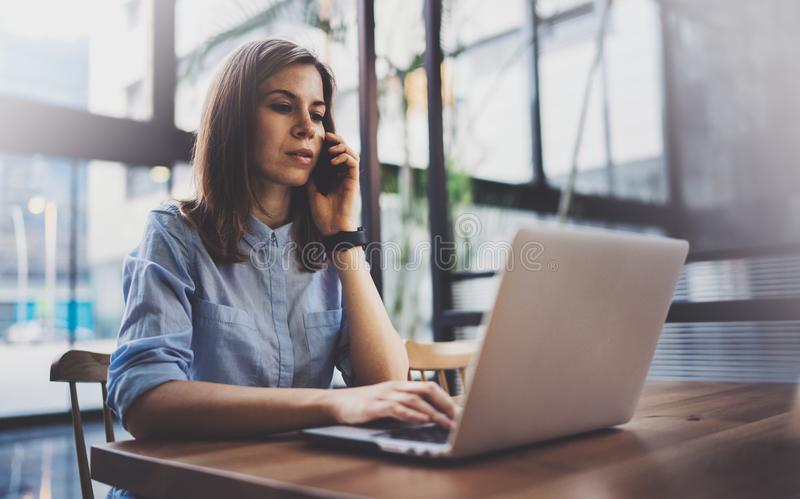 Молодая милая девушка работая на компьтер-книжке и используя передвижной smartphone на ее рабочем месте на современном центре офи стоковое изображение