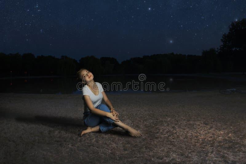 Молодая милая девушка сидя самостоятельно на траве озером под звездным небом лета стоковое фото rf